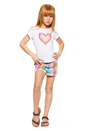 pelirrojas: Longitud total de una ni�a con el pelo rojo en pantalones cortos y una camiseta; aislado en el fondo blanco
