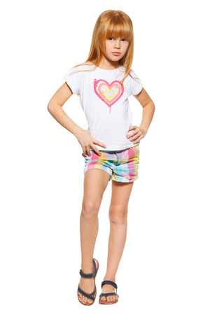 Full length a little girl with red hair in shorts and a T-shirt; isolated on the white background