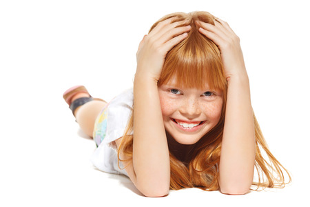 A cheerful little girl with red hair is lying; isolated on the white background