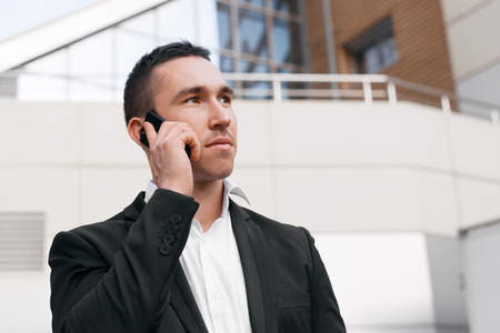 communicative: Young man in black suit talking on mobile phone looking away