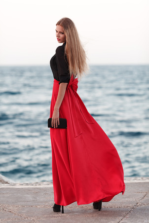 flyaway: Sexy young beauty woman in fluttering red dress at the coast. Fashion woman Stock Photo