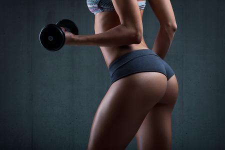 femmes nues sexy: Tr�s jeune sexy beau cul en string. Fitness femme avec des halt�res. Banque d'images