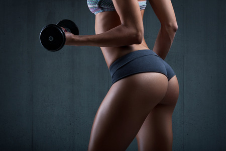 nude ass: Very sexy young beautiful ass in thong. Fitness woman with dumbbells. Stock Photo