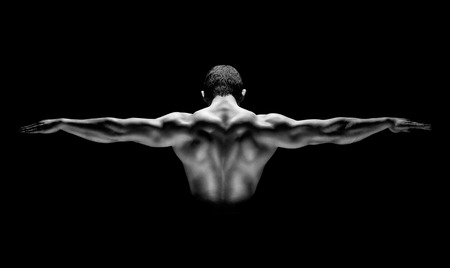 lift hands: Rear view of healthy muscular man with his arms stretched out isolated on black background Stock Photo