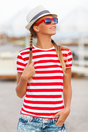 sun tan: Beautiful sexy girl in shorts and striped tshirt in sunglasses in hat outdoors. Tanned woman in summer Stock Photo