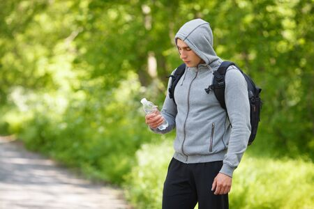 appease: Active man holding a bottle of water, outdoor. Young muscular male quenches thirst Stock Photo
