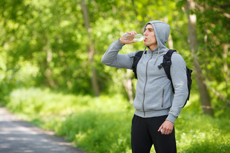 appease: Active man drinking water from a bottle, outdoor. Young muscular male quenches thirst