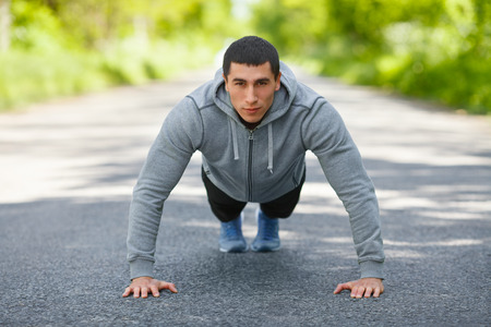sport wear: Fitness man exercising push ups, outdoor. Muscular male cross-training on city park