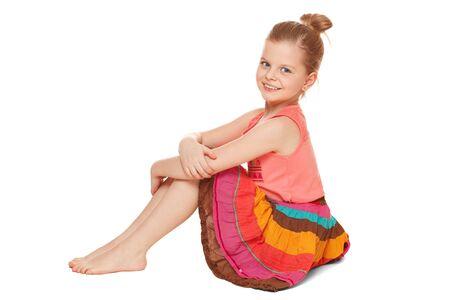 falda: Pequeña muchacha feliz en falda colorida se sienta, aislado en fondo blanco Foto de archivo