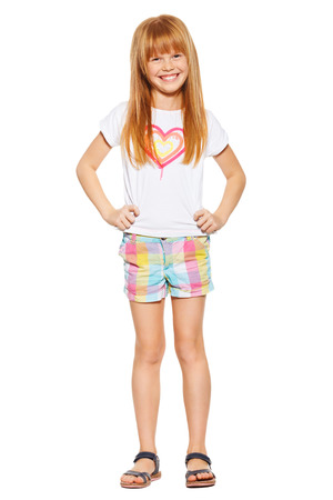 Full length a cheerful little girl with red hair in shorts and a T-shirt; isolated on the white background