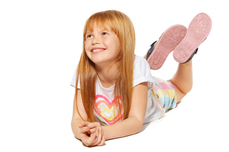 carroty: A cheerful little girl with red hair is lying; isolated on the white background
