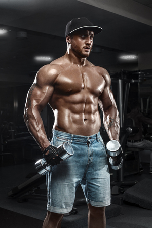 Handsome muscular man with dumbbells working out in gym, doing exercise Stockfoto