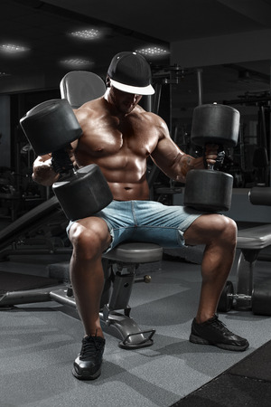 athletic body: Muscular man with big dumbbells working out in gym, doing exercise