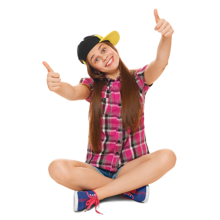 Stylish young girl showing thumbs up in a cap, a shirt and denim shorts. Street style teenager, lifestyle, isolated on white background