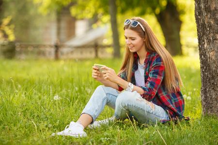 여름 도시 공원에서 휴대 전화에 입력하는 매력적인 웃는 소녀. 현대 행복한 여자와 스마트 폰, 야외