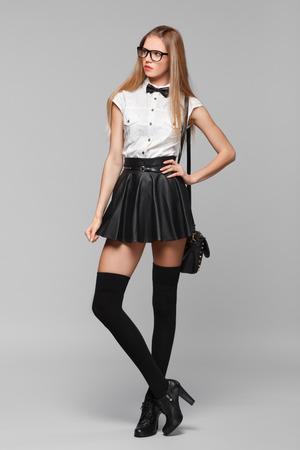 falda: Hermosa mujer está en el estilo de la moda en mini falda negro. Chica de moda