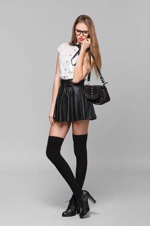 Beautiful woman is in fashion style in black mini skirt. Fashion girl