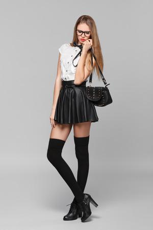 mini falda: Hermosa mujer está en el estilo de la moda en mini falda negro. Chica de moda