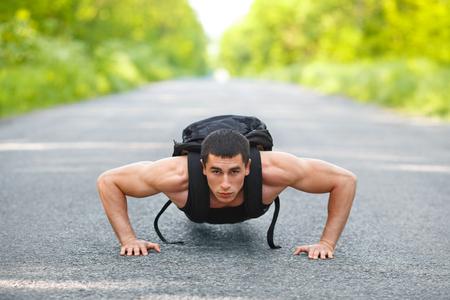 hombre deportista: Hombre de la aptitud que ejercita pectorales, al aire libre. Varón muscular entrenamiento cruzado en parque de la ciudad