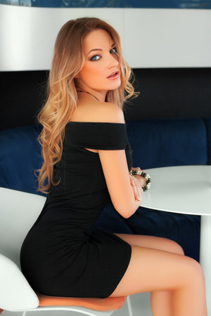 sexy dress: Beautiful sexy woman with black dress and blond hair sitting at the table. Fashion girl