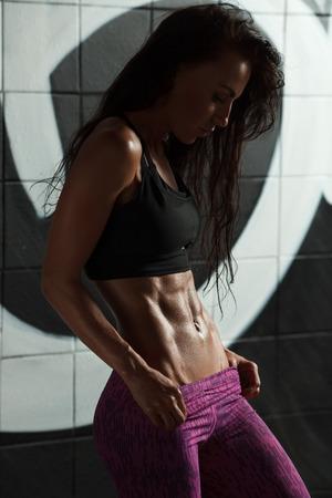 피트 니스 섹시 한 여자 보여주는 abs 및 평면 배꼽. 아름다운 근육질의 소녀, 복부 모양의