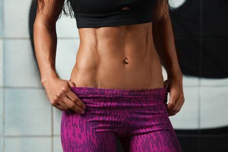 Fitness sexy vrouw zien abs en platte buik. Mooie gespierde meisje, gevormde buik, slanke taille