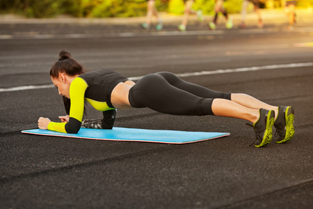 atletismo: Mujer atlética delgada haciendo ejercicio de tablones en el estadio, entrenamiento muchacha deportiva, al aire libre
