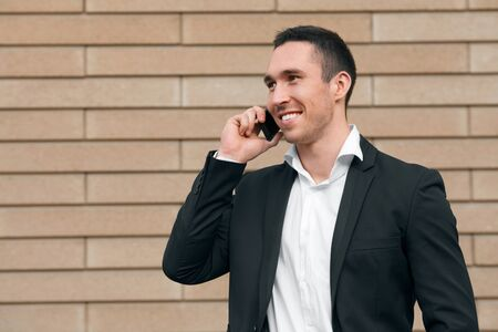 sincere: Smiling happy man talking on mobile phone in a black suit, happy modern man. Outdoors
