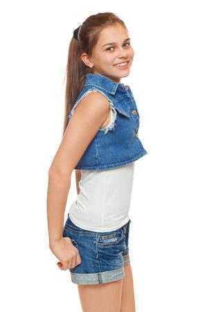 pantalones cortos: Chica joven con estilo en un chaleco vaqueros y pantalones cortos de mezclilla. Adolescente estilo de la calle, estilo de vida, aislado en fondo blanco