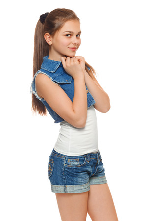 Stylish young girl in a jeans vest and denim shorts. Street style teenager, lifestyle, isolated on white background