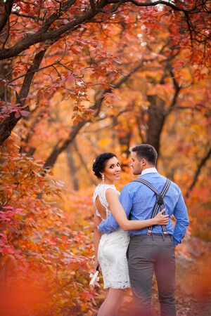 groom and bride: Smiling couple hugging in autumn park. Happy bride and groom in forest, outdoors Stock Photo