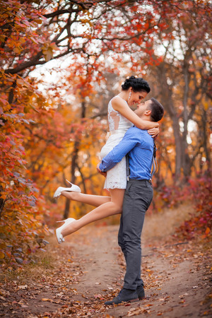 kiss love: Smiling couple hugging in autumn park. Happy bride and groom in forest, outdoors Stock Photo