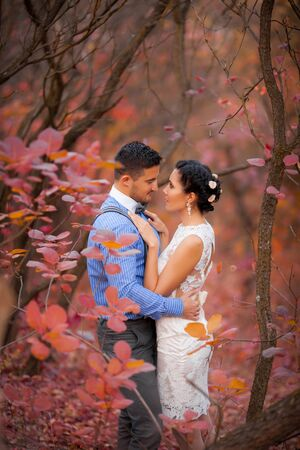romantic couple: Romantic couple hugging in autumn park. Happy bride and groom in forest, outdoors
