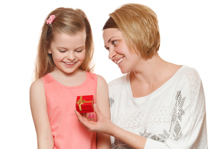 gives: Happy mother and daughter with gift box, Mom gives a gift, isolated on white background Stock Photo