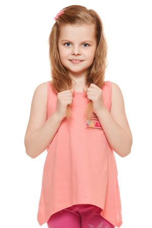 mignonne petite fille: Petite fille mignonne dans une chemise rose tient par la main les cheveux, isolé sur fond blanc