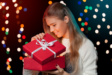 open box: Happy girl opening Christmas box which is glowing inside. Christmas Gift