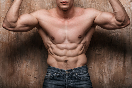 abdominal wall: Muscular man showing abs, on wall background