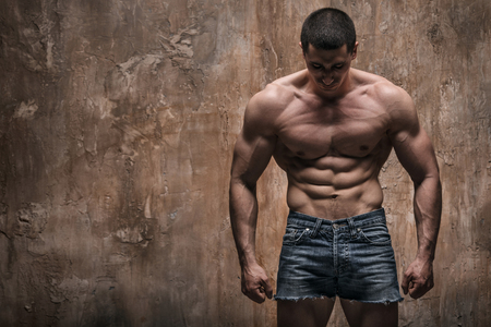 athletic body: Muscular man on wall background