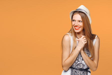 Surprised happy young woman looking sideways in excitement. Isolated over orange background