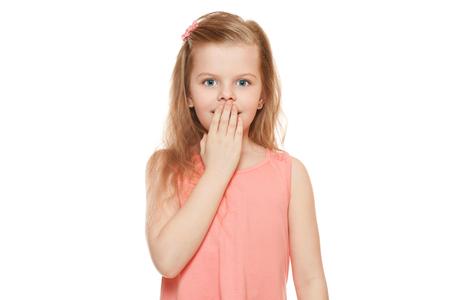 sorprendido: Niña linda sorprendió cerrando su boca, aislado en fondo blanco