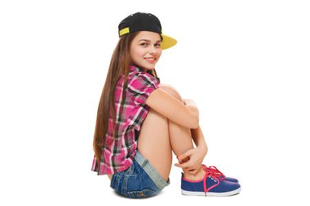 pantalones cortos: Chica joven con estilo con una gorra, una camiseta y pantalones cortos de mezclilla. Adolescente estilo de la calle, estilo de vida, aislado en fondo blanco Foto de archivo
