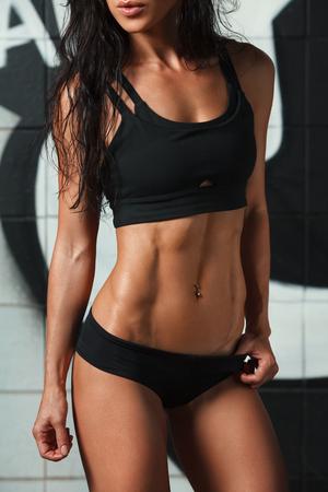 ropa deportiva: Fitness mujer sexy mostrando abdominales y vientre plano. Muchacha muscular que hermoso, abdominal en forma, delgada cintura Foto de archivo
