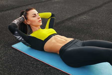 donna di forma fisica che fa sit up nello stadio lavorare fuori. Ragazza sportiva esercizio addominali, all'aperto Archivio Fotografico