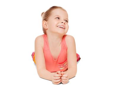 caras felices: Adorable niña divertirse sonriente está acostado mirando para el lado, aislado en fondo blanco