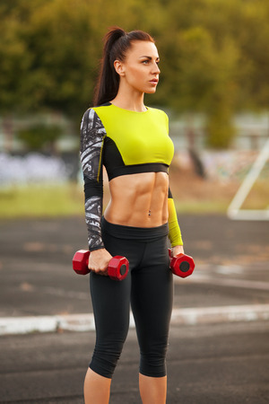 athletics track: Slim athletic woman with dumbbells in the stadium. Sporty sexy girl with flat belly workout, outdoors