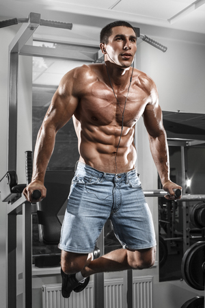 naked abs: Muscular man working out in gym doing exercises on parallel bars, strong male naked torso abs