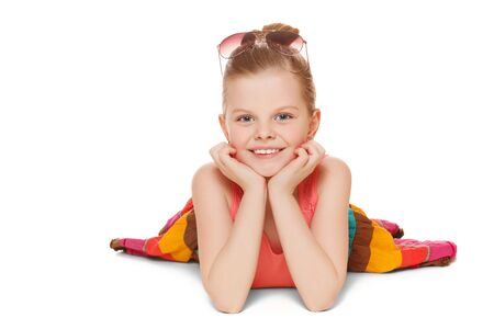 smiling face: Little girl smiling in colorful skirt is lying. Happy child with hands near face, isolated on white background Stock Photo