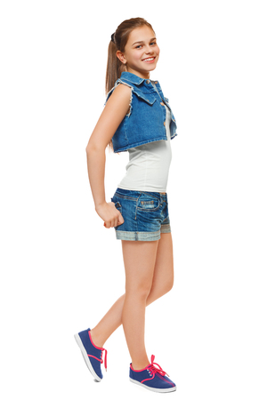 blue jeans kids: Stylish young girl in a jeans vest and denim shorts. Street style teenager, lifestyle, isolated on white background