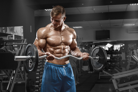 naked abs: Muscular man working out in gym doing exercises with barbell at biceps, strong male naked torso abs
