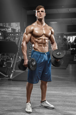 Muscular man working out in gym doing exercises with barbell, strong male naked torso abs Stockfoto